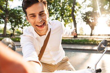 Happy young businessman sitting on a motorbike