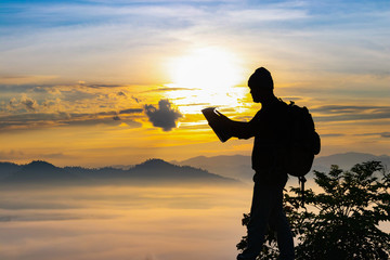 Silhouette traveler man holding map on beauty mountain misty scene background,world tourism day concept