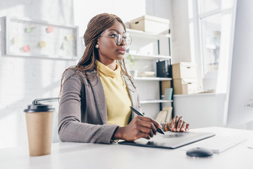 concentrated african american adult businesswoman sitting at computer desk and using graphic tablet at workplace