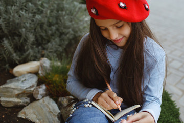 A little girl writes in her outdoor book.