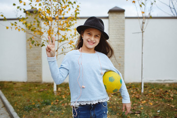 A smiling girl and the ball in her hand.
