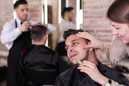 Male getting shave with straight razor in salon