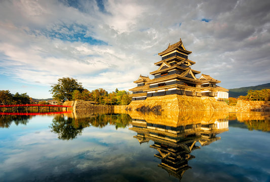 Matsumoto Castle in Matsumoto City Nagano Prefecture In autumn, the change of time from day to night The golden light of the sun shines to the castle with a reflection of the water