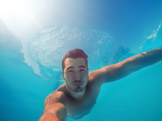 Handsome young man swimming in pool, underwater view