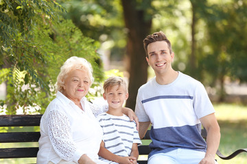 Man with son and elderly mother on bench in park