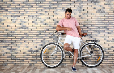 Handsome young hipster man with bicycle near brick wall