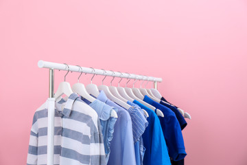 Rack with bright clothes on color background