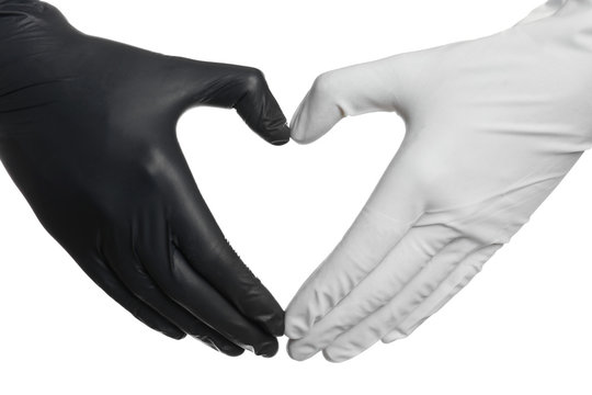 Doctor making heart shape with hands in different medical gloves on white background