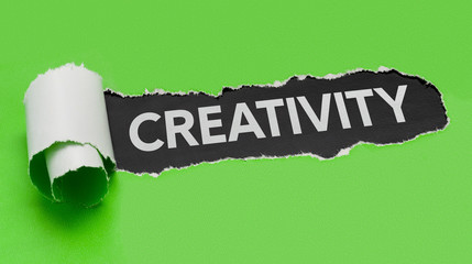 Torn green paper revealing the word Creativity