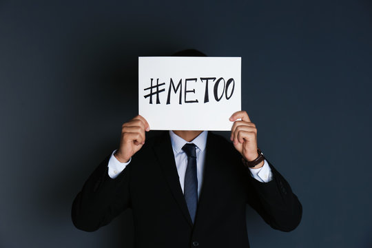 """Man holding paper with text """"#METOO"""" on dark background. Problem of sexual harassment at work"""