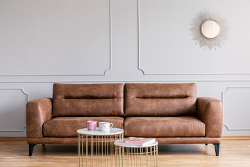 Real photo of a leather sofa, coffee tables and mirror in a living room interior