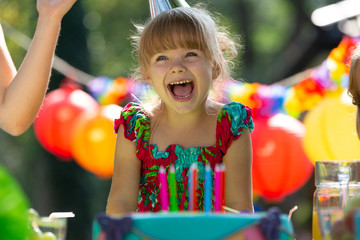 Smiling girl wearing colorful dress blowing out candles on birthday cake during party