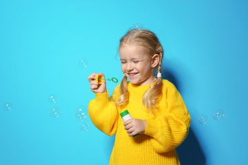 Cute little girl blowing soap bubbles on color background