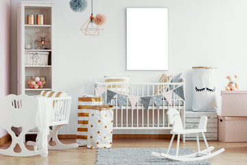 Empty mockup poster on the wall of interior with white wooden rocking horse, crib and nursery with white and gold accents, real photo