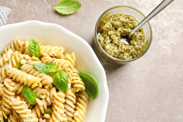 Plate of delicious basil pesto pasta served for dinner on table, flat lay