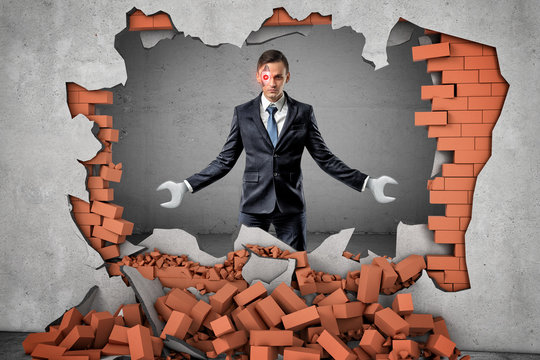 Robotized businessman with spanner hands breaking red brick wall on grey background