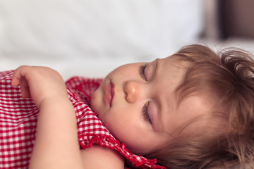 Close up portrait of a beautiful nine month old baby girl sleeping on blurred background. Sleeping child face. Cute infant kid. Child portrait in pastel tones. Selective focus.