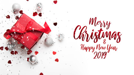 Merry Christmas and Happy Holidays greeting card. New Year. Red gift, present on white background top view. Winter holidays.