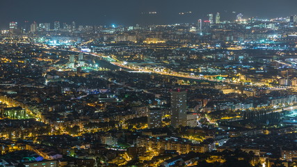 Barcelona and Badalona skyline with roofs of houses and sea on the horizon night timelapse