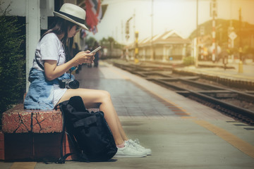 Tourist women holding looking for smartphone with backpack waiting for train at station in the evening.