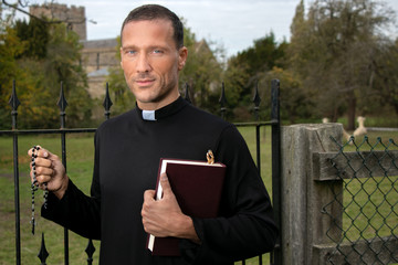 Good looking priest standing next to iron gate holding bible with field, alpacas and church in background