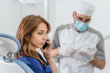 the girl at the reception at the dentist talking on the phone. The doctor is upset with the patient's behavior