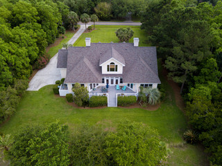 Aerial view of large home with new roof on wooded grassy property Wall mural