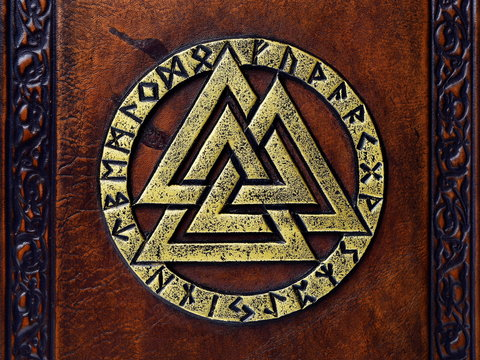 Vintage leather book with gilded Odin's symbol, surrounded with runes. English translation of the runes is: A B C D E F G H I J K L M N O P Q R S T U V W X Y Z
