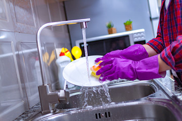 Housewife in rubber colored gloves washing dishes with a yellow sponge in the kitchen at home.