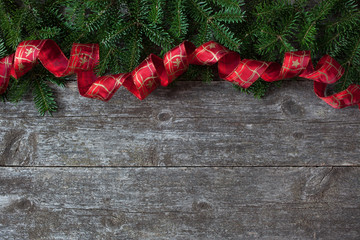 Christmas wooden background with fir branches and red ribbon