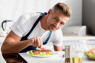 adult man decorating cooked steak with chili pepper