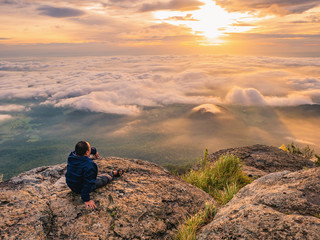 Trekker sitting on the mountain with Beautiful Sunrise and sea of mist in the morning on Khao Luang mountain in Ramkhamhaeng National Park,Sukhothai province Thailand