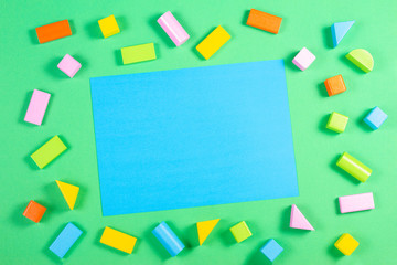 Toys background with blank blue card and colorful wooden cubes pattern on green color background
