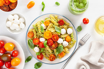 healthy fusilli pasta with pesto sauce, roasted tomatoes, mozzarella