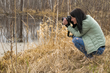 A girl in a warm jacket in the spring photographs objects near the pond