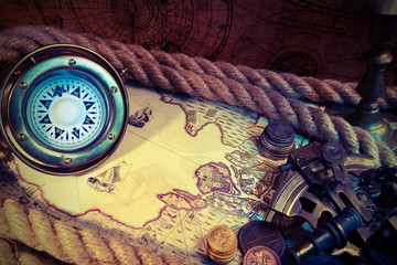 Old ship compass,coins,rope,pirate world map. Travel and marine engraving background. Treasure hood concept. Vintage style.