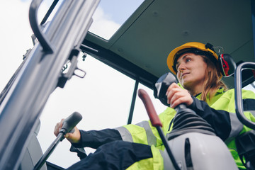 low angle view of Woman driving heavy equipment