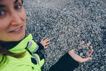 High angle view of woman in safety clothing holding gravel