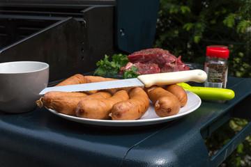 Ein Teller voller Würstchen und eine Schüssel mit Rindfleisch, das gleich gegrillt wird.