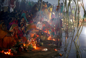 Hindu devotees prepare to worship the Sun god on the banks of the Sabarmati river during the religious festival of Chhath Puja in Ahmedabad