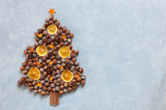 Original Christmas tree made of hazelnuts on a wooden table. Top view, close-up.  Christmas, New Year concept on light gray concrete background