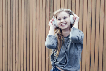 Cute girl listening to music in white wireless headphones on the background of the brown board. Electronic music. Musical style. Pleasant sounds. The pleasure of sound.