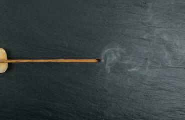Burning incense aroma sticks with smoke on black background
