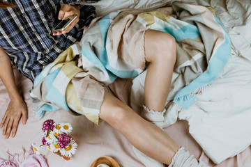 Cozy flatlay with white tanned woman in white socks sitting in her bed holding a smartphone