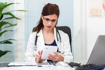 Beautiful female doctor in her studio using a digital tablet