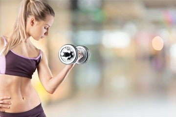 Close-up attractive young woman holding dumbbell on blurred