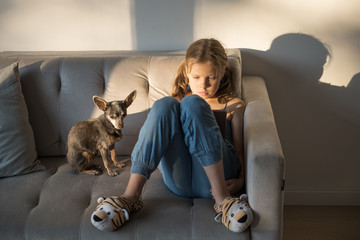 Little girl with device on couch
