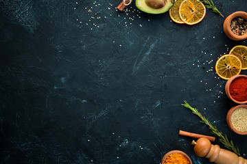Wall Mural - Colored spices on a black stone background. Free space for your text. Top view.