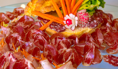 Parma ham sliced and placed on a tray with garnish of fresh vegetables