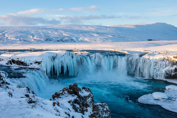 Frozen Godafoss waterfall on cold winters day at dawn, Northern Iceland